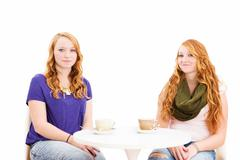 charming young redhead women sitting at a coffee table - stock photo