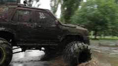 Large bigfoot car completely in dirt turns around mud puddle, click for HD Stock Footage