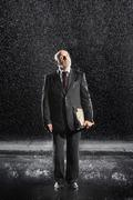 Middle Aged Businessman With Binder In Rain Stock Photos