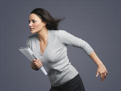 Determined Young Businesswoman Running Into Wind - stock photo
