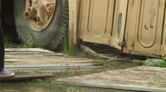 Big puddle, natural disaster rain. Legs passing by school bus, click for HD Stock Footage
