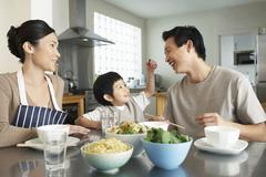Happy Young Family Enjoying Meal Stock Photos