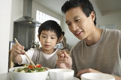 Father Watching Son Trying To Use Chopsticks - stock photo