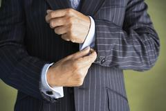 Midsection Of Man In Suit Buttoning Cuff Sleeves - stock photo