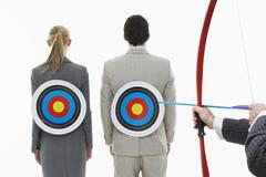 Aiming Arrow At Targets On Business people's Backs - stock photo