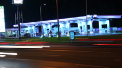 Fueling station night view timelapse, car leave red light traces, click for HD Stock Footage