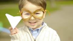 Little Boy Holds Up His Paper Airplane And Smiles - stock footage