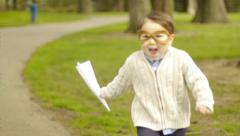 Little Boy Runs In Park With His Paper Airplane - stock footage