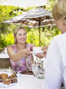 Stock Photo of Woman Passing Tea Cup To Friend At Outdoor Cafe