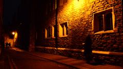 People walking on a dark poorly light street Stock Footage