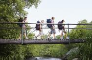Stock Photo of Teenagers With Backpacks Walking On Bridge