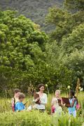 Teacher With Children Preparing Notes During Field Trip - stock photo