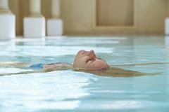 Woman Floating In Swimming Pool Stock Photos