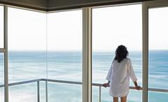 Stock Photo of Woman Looking At Sea View From Balcony