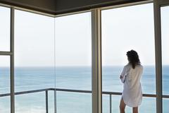 Stock Photo of Woman Looking At Ocean View From Balcony