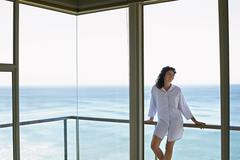 Woman Looking Away While Leaning On Railing In Balcony - stock photo