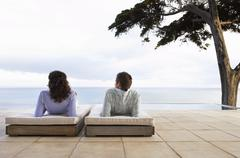 Couple Relaxing On Sunbeds By Infinity Pool - stock photo