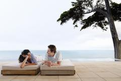 Happy Couple Relaxing On Sunbeds By Infinity Pool - stock photo