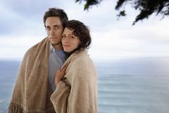 Stock Photo of Romantic Couple Wrapped In Blanket Standing Against Sea