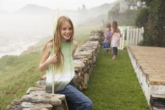 Happy Girl With Fishing Net Sitting On Stone Wall At Yard - stock photo