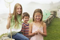 Stock Photo of Cute Siblings With Fishing Nets At Yard