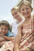 Happy Little Siblings Sitting Together Stock Photos
