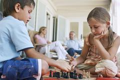 Little Siblings Playing Chess At Porch - stock photo
