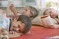Boy Smiling With Sisters Reading Books At Porch Stock Photos
