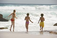 Little Siblings Running In Water - stock photo