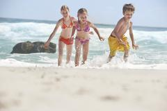Cheerful Siblings Running In Water Stock Photos