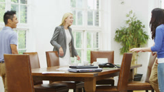 Attractive casual business team take their seats at a table for a meeting - stock footage