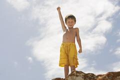 Little Boy With Hand Raised Standing On Rock - stock photo