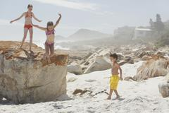 Girl Jumping From Rock While Playing With Siblings - stock photo