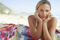 Stock Photo of Woman With Head In Hands Lying On Blanket At Beach