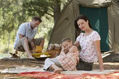 Parents With Daughter Sitting At Campsite - stock photo