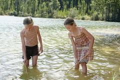 Girls Exploring Bottom Of Lake With Sticks - stock photo