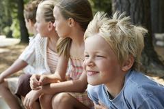 Children Sitting In Forest Stock Photos
