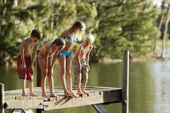 Children In Swimwear Standing On Jetty By Lake Stock Photos