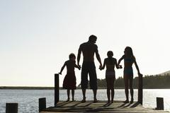 Family Standing On Edge Of Jetty - stock photo