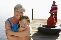 Senior Woman Hugging Grandson On Jetty Stock Photos