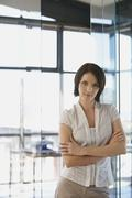 Stock Photo of Businesswoman Standing Arms Crossed In Office