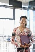 Happy Businesswoman With File Folder In Office - stock photo