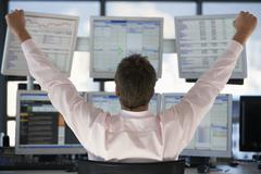 Stock Trader Watching Computer Screens With Hands Raised Stock Photos