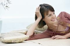 Stock Photo of Woman Relaxing On Sofa Outdoors