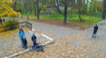 Flight in autumn park with people.  Aerial Footage