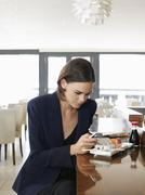 Businesswoman Text Messaging In Sushi Restaurant - stock photo