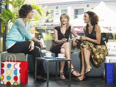 Friends Gossiping At Outdoor Cafe - stock photo