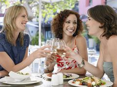 Friends Toasting Wine At Outdoor Cafe - stock photo