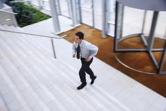 Businessman Running Upstairs In Office Lobby - stock photo