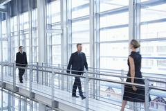 Business People Walking By Railing In Modern Office Stock Photos